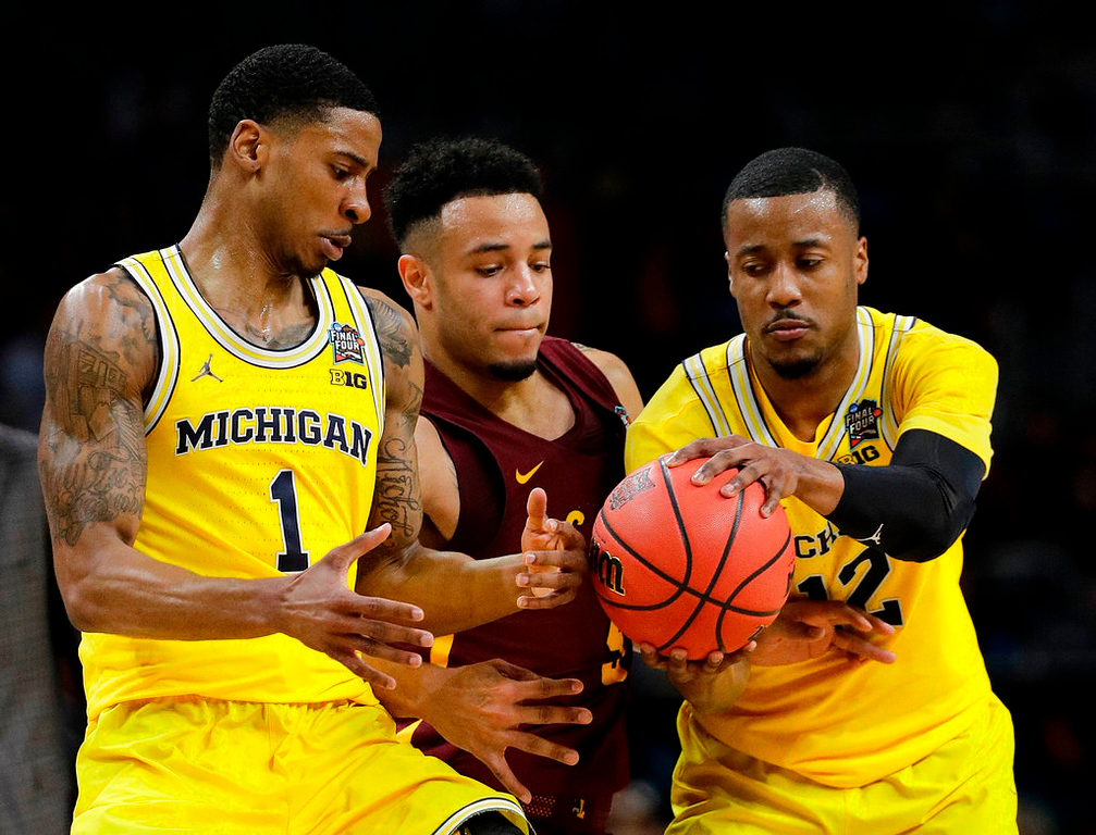 . Loyola-Chicago\'s Marques Townes (5) battles for the ball against Michigan\'s Charles Matthews (1) and Charles Matthews (1) during the first half in the semifinals of the Final Four NCAA college basketball tournament, Saturday, March 31, 2018, in San Antonio. (AP Photo/David J. Phillip)