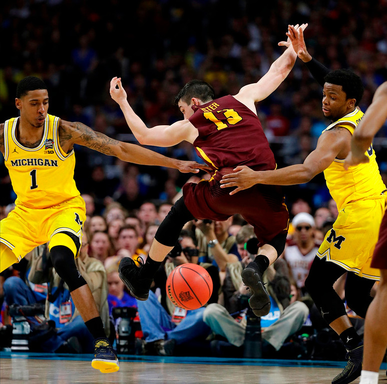 . Loyola-Chicago\'s Clayton Custer (13) loses the ball against Michigan\'s Charles Matthews (1) and Zavier Simpson during the second half in the semifinals of the Final Four NCAA college basketball tournament, Saturday, March 31, 2018, in San Antonio. (AP Photo/David J. Phillip)