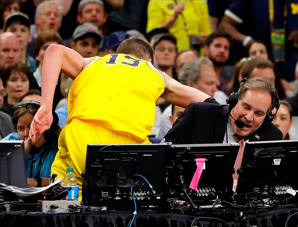 . Michigan\'s Moritz Wagner (13) jumps over the broadcast table during the second half in the semifinals of the Final Four NCAA college basketball tournament against Loyola-Chicago, Saturday, March 31, 2018, in San Antonio. (AP Photo/Eric Gay)