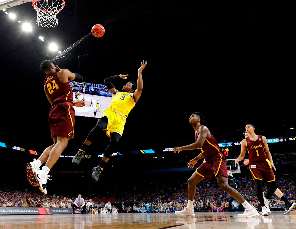 . Michigan guard Zavier Simpson (3) shoots over Loyola-Chicago forward Aundre Jackson (24) during the second half in the semifinals of the Final Four NCAA college basketball tournament, Saturday, March 31, 2018, in San Antonio. (AP Photo/David J. Phillip)
