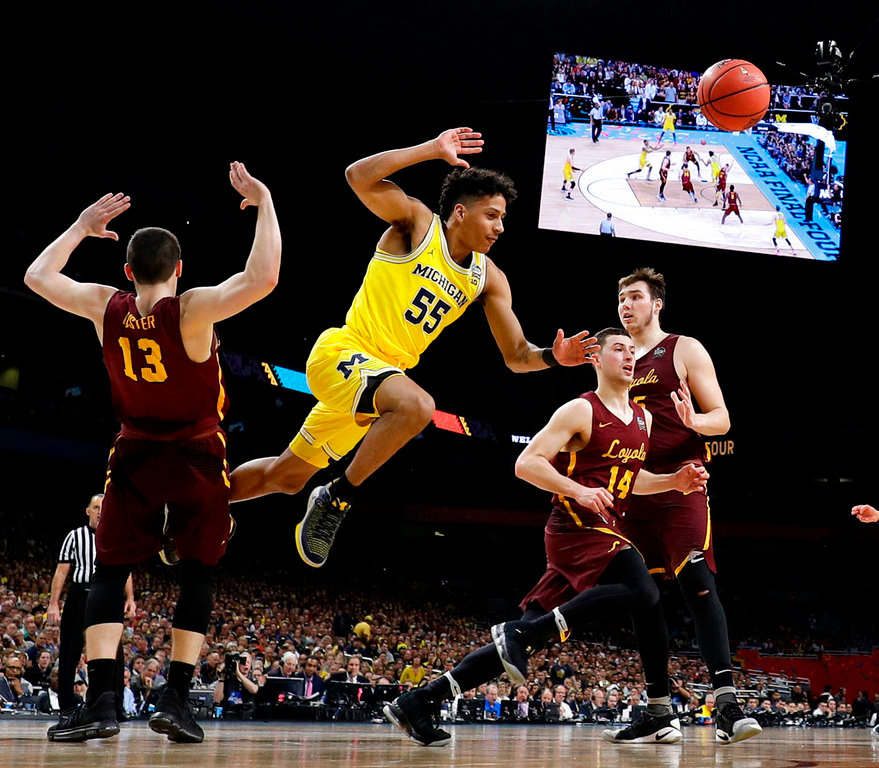 . Michigan guard Eli Brooks (55) fights for a rebound with Loyola-Chicago\'s Clayton Custer (13) and Ben Richardson (14) during the first half in the semifinals of the Final Four NCAA college basketball tournament, Saturday, March 31, 2018, in San Antonio. (AP Photo/Eric Gay)