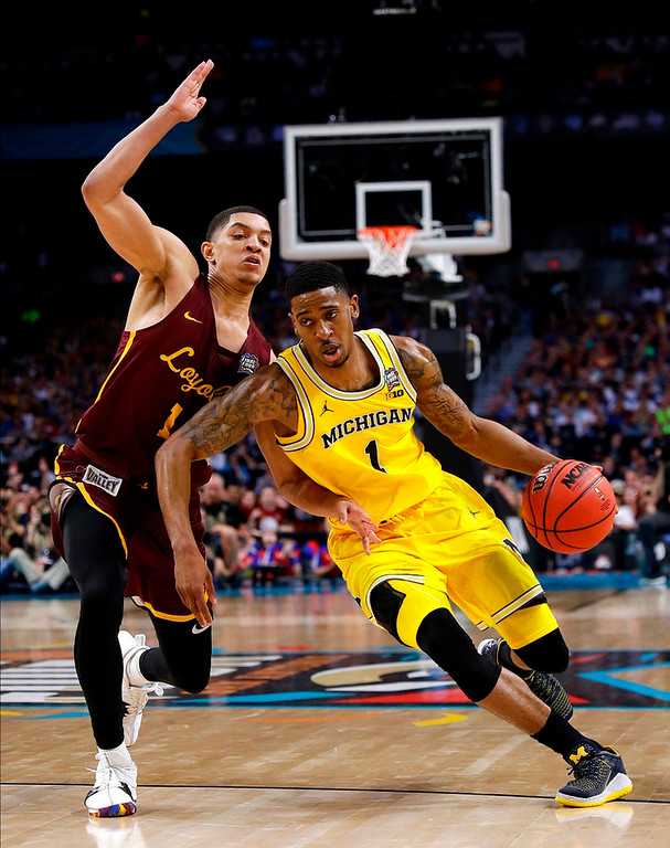 . Michigan guard Charles Matthews drives past Loyola-Chicago guard Lucas Williamson, left, during the second half in the semifinals of the Final Four NCAA college basketball tournament, Saturday, March 31, 2018, in San Antonio. (AP Photo/David J. Phillip)