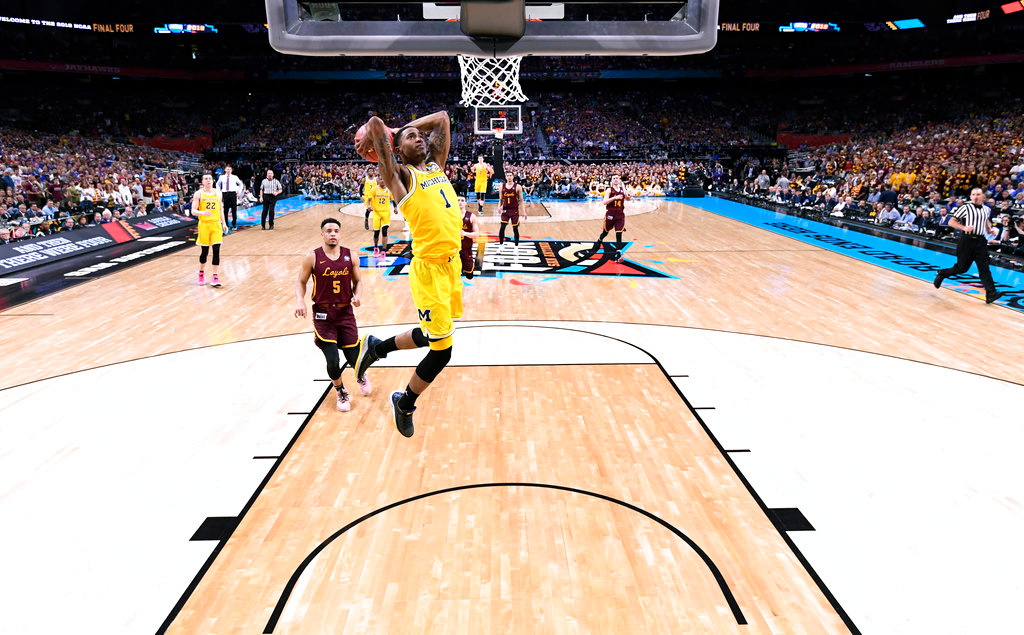 . Michigan guard Charles Matthews (1) dunks the ball ahead of Loyola-Chicago guard Marques Townes (5) during the second half in the semifinals of the Final Four NCAA college basketball tournament, Saturday, March 31, 2018, in San Antonio. Michigan won 69-57. (AP Photo/Chris Steppig, NCAA Photos Pool)