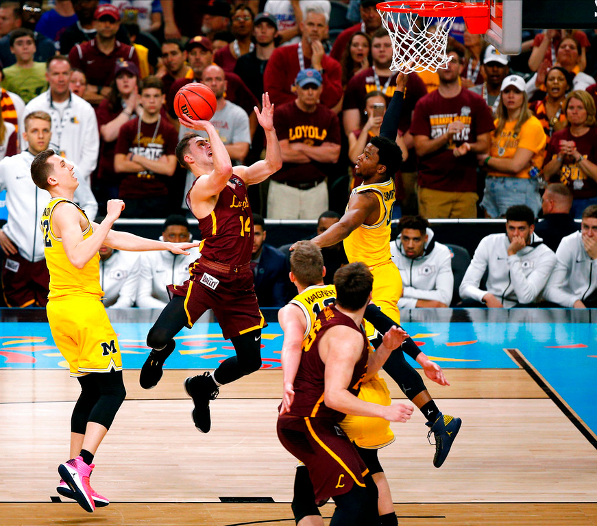 . Loyola-Chicago guard Ben Richardson, center, drives to the basket between Michigan defenders Duncan Robinson, left, and Zavier Simpson during the second half in the semifinals of the Final Four NCAA college basketball tournament, Saturday, March 31, 2018, in San Antonio. (AP Photo/Brynn Anderson)