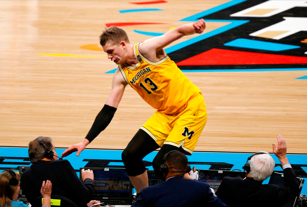 . Michigan\'s Moritz Wagner (13) jumps over the broadcast table during the second half in the semifinals of the Final Four NCAA college basketball tournament against Loyola-Chicago, Saturday, March 31, 2018, in San Antonio. (AP Photo/Brynn Anderson)