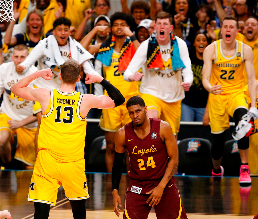 . Michigan\'s Moritz Wagner (13) celebrates with his teammates as Loyola-Chicago\'s Aundre Jackson (24) walks off during the second half in the semifinals of the Final Four NCAA college basketball tournament, Saturday, March 31, 2018, in San Antonio. (AP Photo/Brynn Anderson)