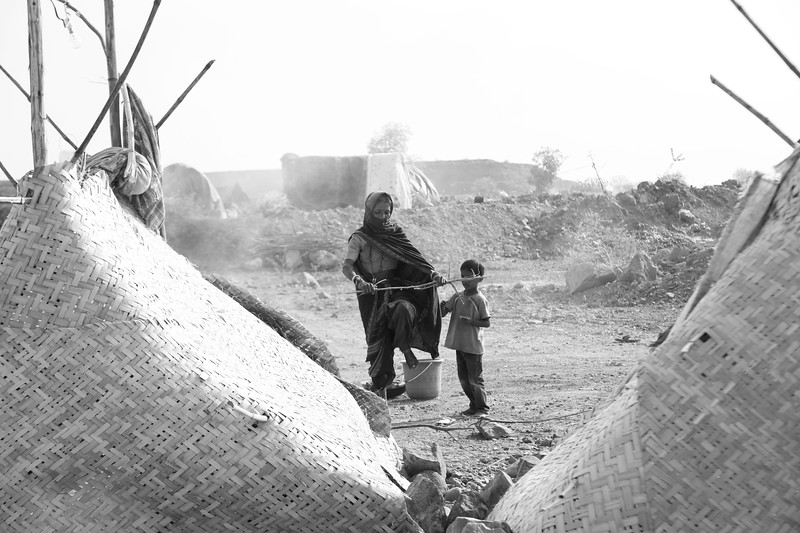 Woman and child living in the thatched houses on the construction site, the temperature in summer rises up to 50 degree celsius.