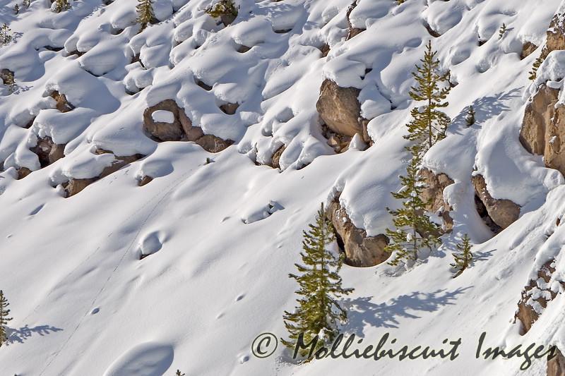Snow shapes on rocky hillside.