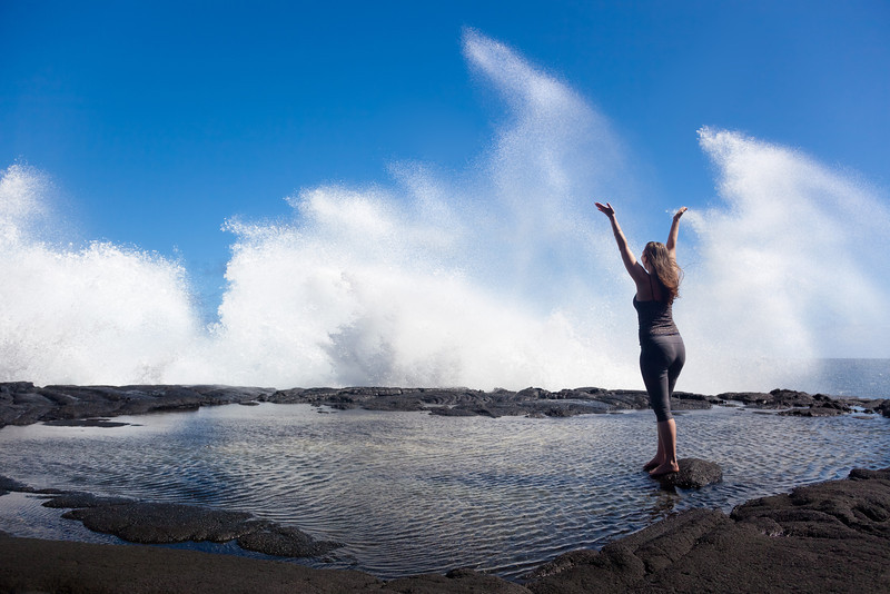 """ARISE!""  The Big Island, Hawaii  Massive, wind-driven waves slam into the dried lava shore, shaking the very ground and causing water to skyrocket above a woman lucky enough to witness it all."