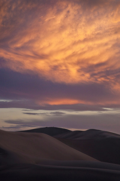 "<b>""ATOP HIGH DUNE""</b>  Great Sand Dunes National Park, Colorado  Several adventurous souls sit atop High Dune -- the second tallest dune in the park -- as the clouds above explode with the colors of sunset."