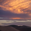 """<b>""""ATOP HIGH DUNE""""</b>  Great Sand Dunes National Park, Colorado  Several adventurous souls sit atop High Dune -- the second tallest dune in the park -- as the clouds above explode with the colors of sunset."""