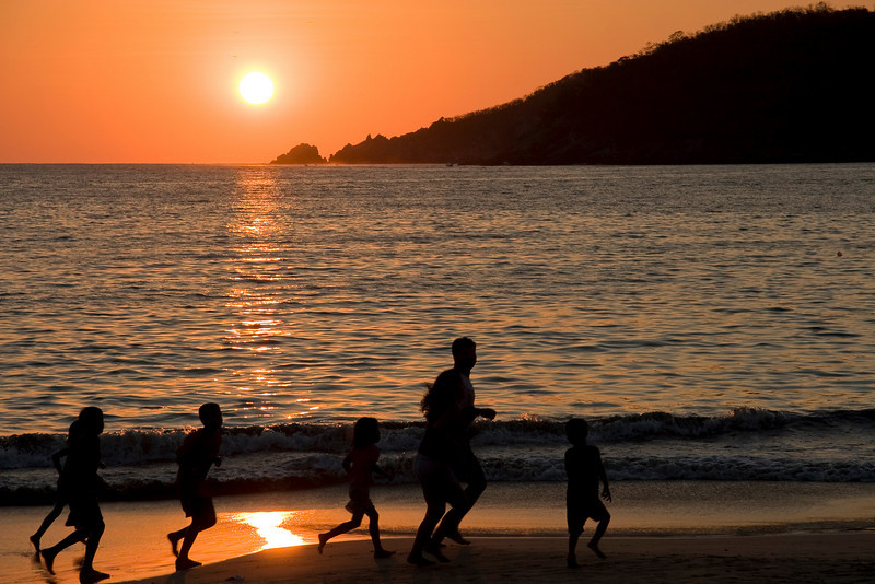 "<b>""FROLICKING FAMILY""</b>  Zihuatanejo, Mexico  A family runs down the beach at sunset."