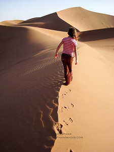 Barefooted trekking in the sand dunes of Erg Chigaga, Morocco.