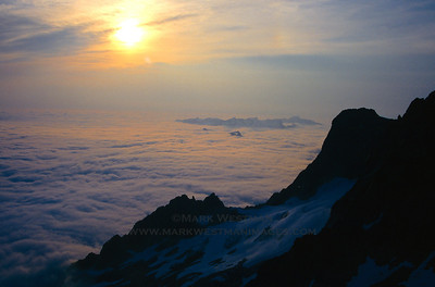 Evening sun over cloud sea, wildfire smoke, and Early Morning Spire in North Cascades National Park, Washington.