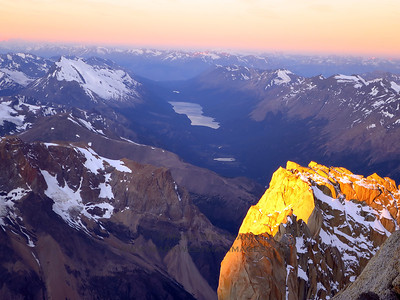 Sunset illuminates the summit of Aguja Mermoz as viewed from high on Fitzroy's north pillar. Lago Del Desierto visible below.