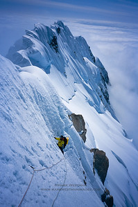 Forrest Murphy on steep snow traversing beneath large cornices on Mount Hunter's south ridge. Our tracks are visible on the ridge in the background.