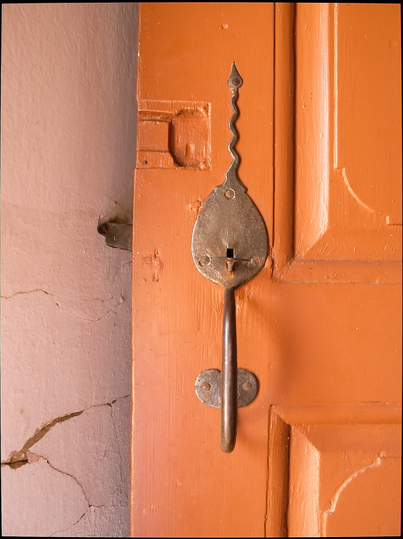 Antique hand made door latch on orange door, Bornholm, Denmark.