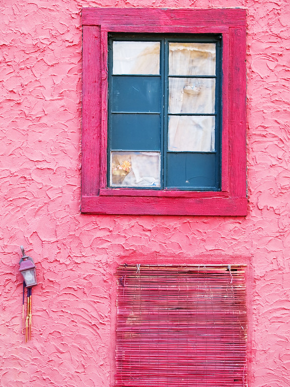 Blue window in magenta stucco wall in Cottonwood Arizona