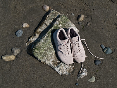 White running shoes and stones on beach
