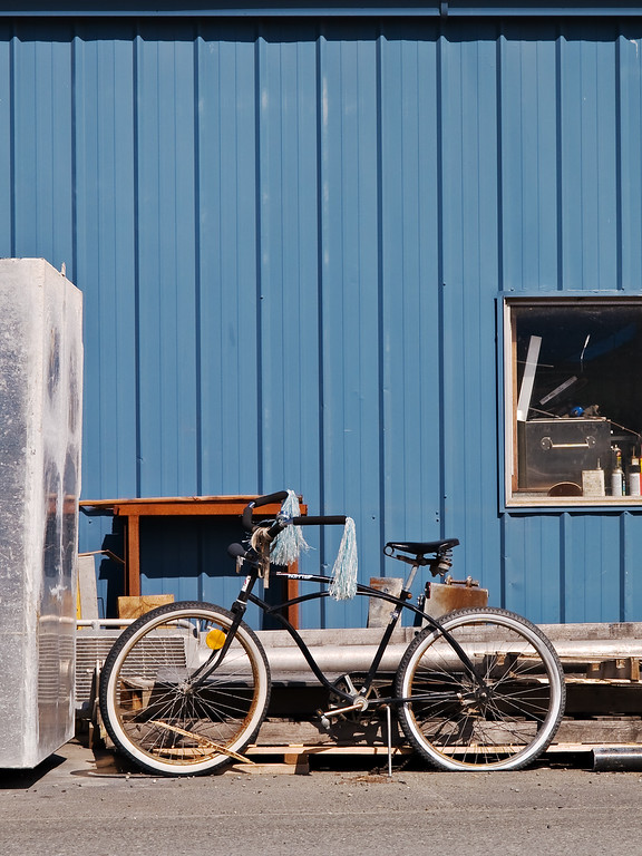 Black bicycle and junk against blue industrial wall