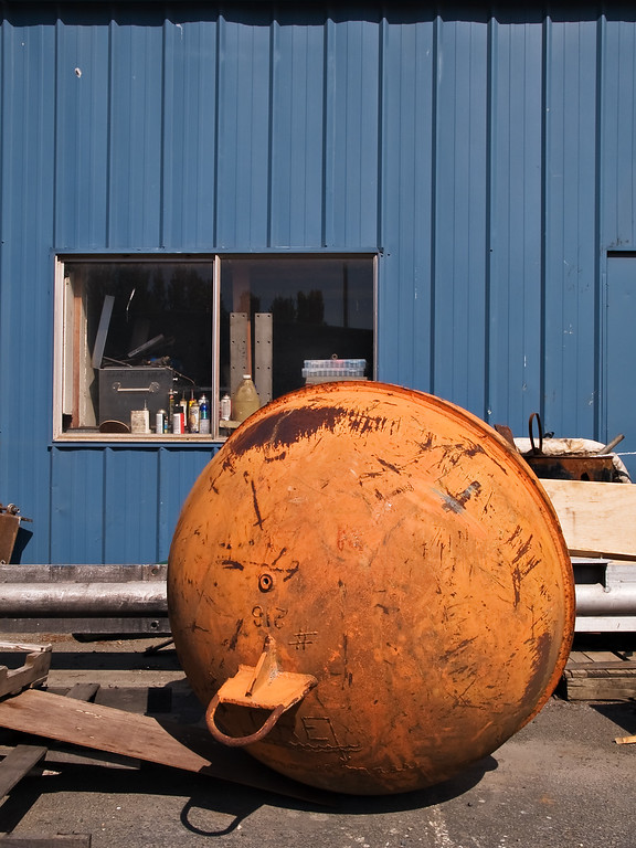 Orange commercial fishing float and blue industrial wall
