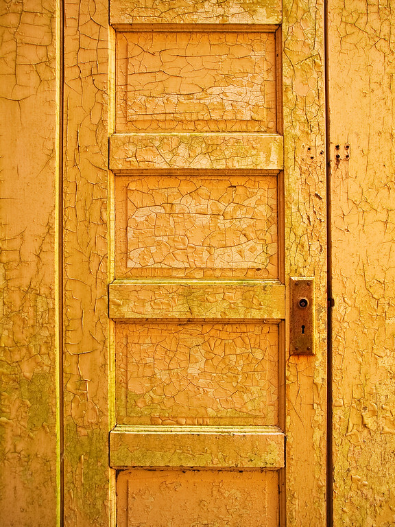 Weathered yellow door, cracked paint, California