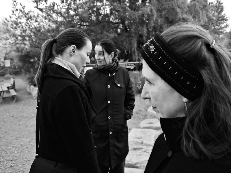 Three women in black coats park winter