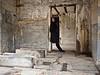 Woman in black coat in concrete room