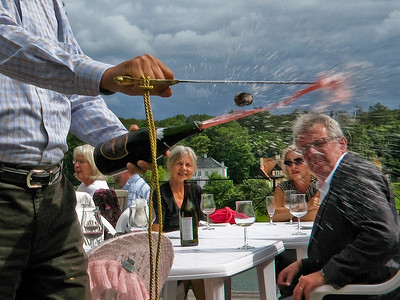Opening a champagne bottle with a sword at a wine tasting party in  Holte, Denmark.