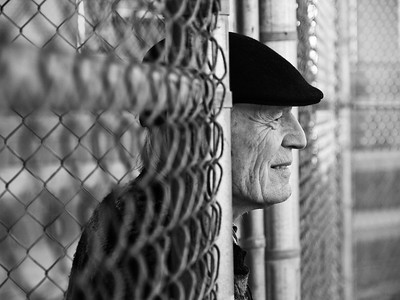 Senior man chain link fence black hat