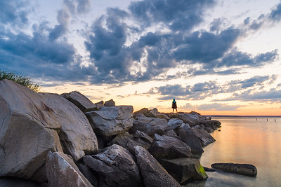 Girl watching sunset on a jetty (landscape)