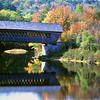A covered bridge in Henneker, New Hampshire passws over the Contocook River in the fall, USA