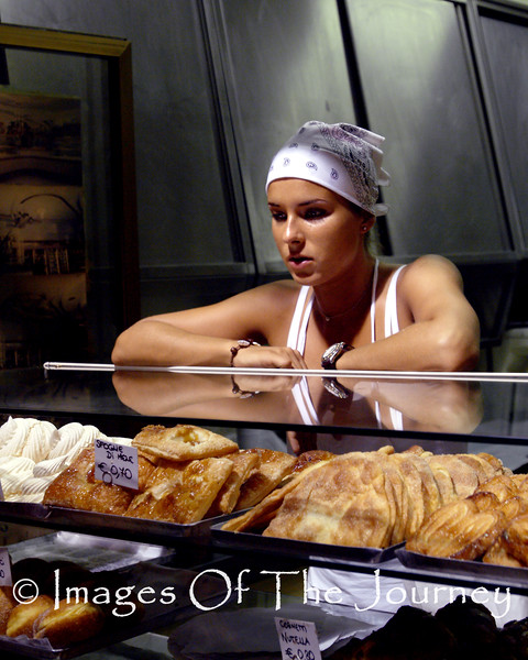 Madonna Of The Bakery.......<br /> In the summer of 2003, there was a heat wave in Europe. It was so unbearable that most businesses closed during the searing heat of the afternoon and then reopened in the evening and then staying open until well after midnight. <br /> <br /> I had just landed at Leonardo Da Vinci airport, picked up my rental car (with AC thank god) and headed south to try to find the hotel I had booked on the Internet. I have a confession to make. I travel all over the world and regularly get lost if there is a choice of more than one road I will take the wrong one. So after about 3 tries I finally found my hotel in the town of Pommesia south of Rome. With the time change I was not yet feeling sleepy so I went for a walk along the main road next to the beach. As I walked along I caught sight of a bakery with a sales window open to the street. In that window was this gorgeous woman that you see here. She had no idea I was leaning on a lamppost (to steady my camera) and took her photo as she stared pensively out into the darkness. <br /> <br /> I decided to use no flash and so set the camera (Fuji S2 SLR Nikon based) and this photo was the result. <br /> <br /> It is now one of my favourite photos that I have ever taken. <br /> <br /> The natural lighting was amazing, outlining every muscle and particularly the shaft of light on her head giving her a type of halo... thus the name of the photo Madonna Of The Bakery.<br /> One other detail... it was after midnight and a sign nearby was flashing a temperature reading 36C. (97F)