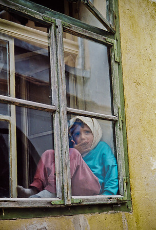 Girl in Window, Sighisoara, Romania, 2000 Color, 35mm.  At a street festival in Sighisoara, I noticed this girl watching the festival from her window while nibbling on lunch.
