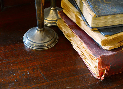 A stack of dusty and worn old books with tarnished candlesticks on a rugged worn wooden table. The whole scene shows dust, neglect and age. The candlesticks are casting shadows on the books from sidelighting
