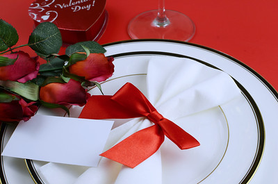 Simple place setting for Valentine's Day with black and white china, silk red roses, a bow on a red background. Shiny candy box and stem of wine glass at edge. Copy space on blank card