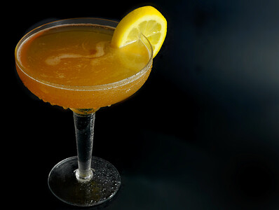 A whisky sour in a coupe glass with a lemon wagon wheel garnish on a round table with a dark background