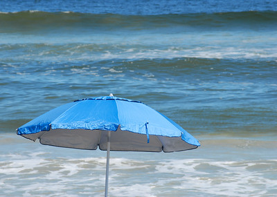 Selevtive focus is on a bright blue beach umbrella that is ruffled by the wind at the beach where waves can be seen rolling into shore