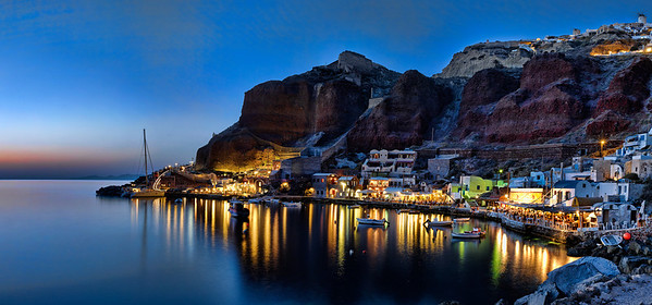 Twilight panorama of Ammoudi Bay in Santorini, Greece.  The town of Oia is seen above on the cliffs.