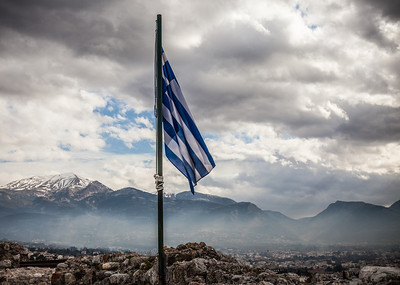 The Greek flag waves from the Castro in Patra, Greece against a background of snow capped mountains.