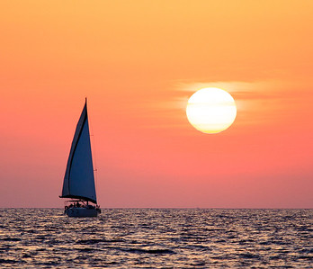 A gorgeous sunset behind a sailboat in the waters of Santorini, Greece.