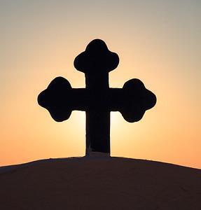 A church cross at sunset in Santorini, Greece.