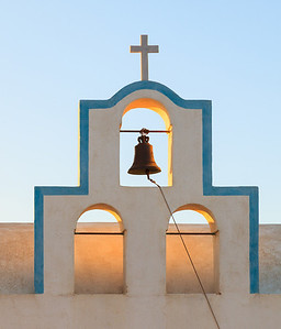 Sunrise backlights a church bell in Santorini, Greece.