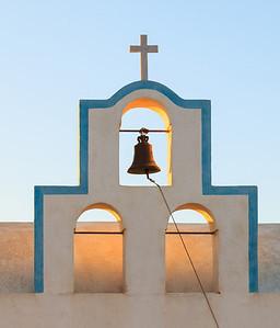 Sunrise backlights a church bell in Santorini, Greece.