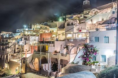 Fog climbs up the mountainside over the town Imerovigli in Santorini, Greece.