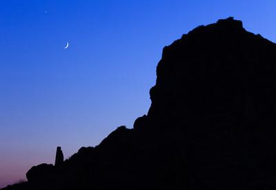 The moon over Skaros Rock from Imerovigli in Santorini, Greece.