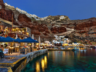 Twilight image of Ammoudi Bay in Santorini, Greece.  The town of Oia is seen above on the cliffs.