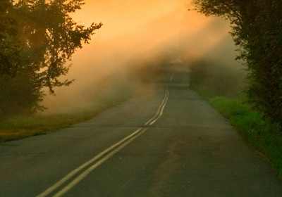 The sunrise reflecting through the morning mist on a country road.