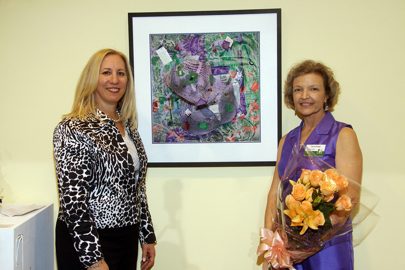 """September 9, 2009. With the bouquet from my radiation oncologist at the Courage Unmasked art auction, I'm standing with oral surgeon Harlene, who bought my mixed media radiation mask sculpture. I named it """"Blooming Passage"""" in reference to my journey as a patient of oral cancer, and it now hangs in Harlene's office reception area."""