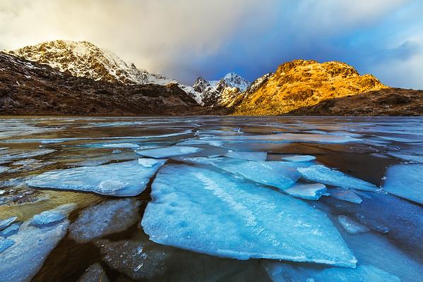 Photo of ice in frozen Solstadvatnet Lake during sunset in Lofoten, Norway
